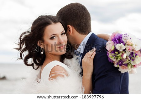 Happy newlyweds on the beach. Portrait of loving bride and groom near the sea. - stock photo