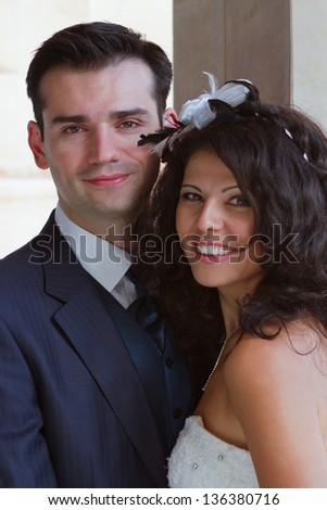 Happy newlyweds posing outdoors after their wedding - stock photo