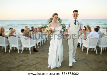 Happy newlyweds walk from wedding altar on the sea shore