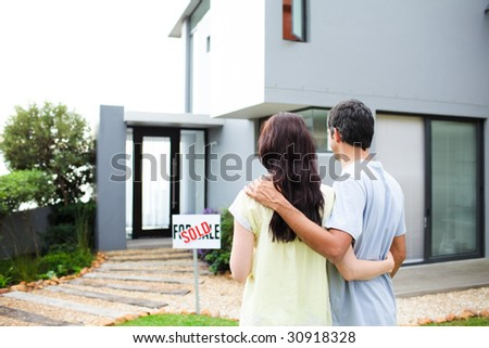 Happy newlyweds with their new house - stock photo
