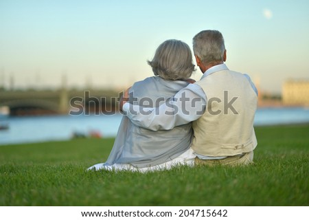 Happy nice mature couple looking at town - stock photo