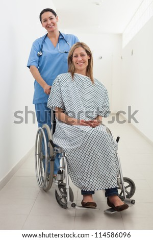 Happy nurse and patient in wheelchair in hospital corridor - stock photo
