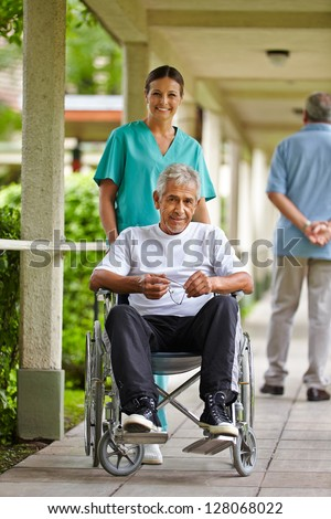 Happy nurse driving a senior man in wheelchair in a clinic - stock photo