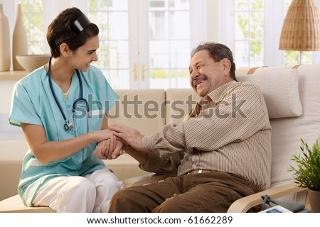 Happy nurse holding hands of elderly patient sitting side by side at home, laughing.? - stock photo