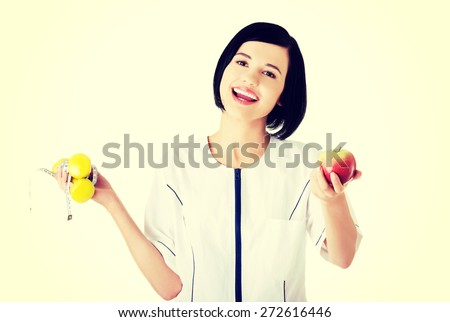 Happy nutritionist holding lifts and apple - stock photo