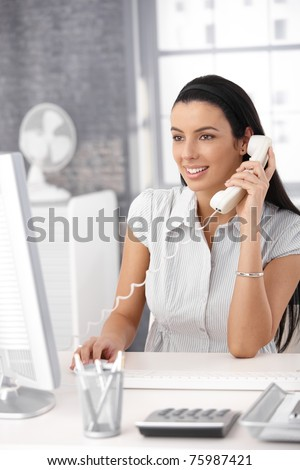 Happy office girl at desk working on desktop computer, using landline phone, smiling.?