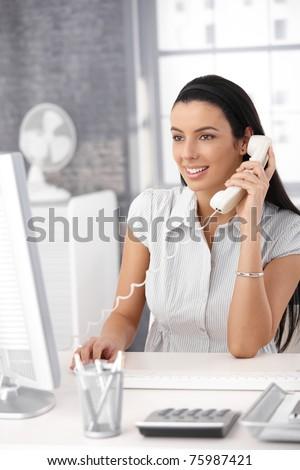 Happy office girl at desk working on desktop computer, using landline phone, smiling.? - stock photo