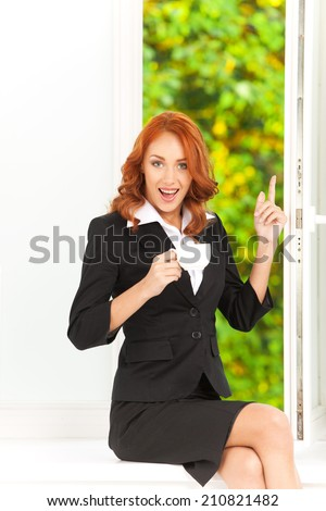 happy office girl sitting on windowill. red hair girl enjoying cup of coffee and view  - stock photo