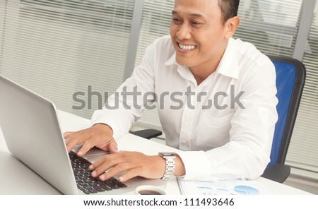 Happy office worker sitting at the table and working with laptop - stock photo