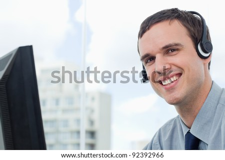 Happy office worker using a headset his office - stock photo