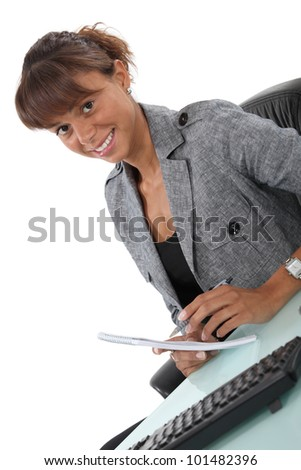 Happy office worker writing at her desk - stock photo