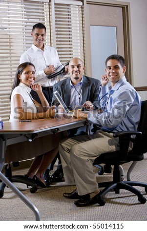 Happy office workers meeting at table in boardroom working together - stock photo