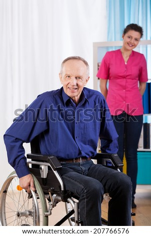 Happy old and disabled man on a wheelchair