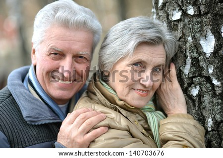 happy old couple on a walk in nature in autumn