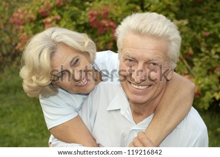 happy old couple posing at summer park
