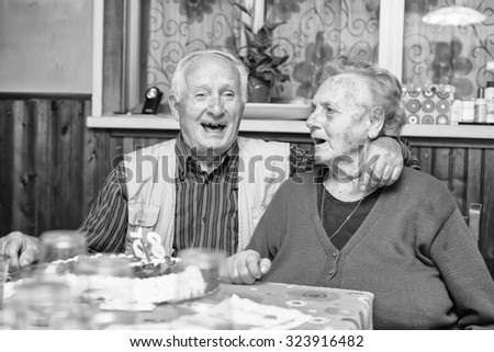 Happy old couple smiling in their home.