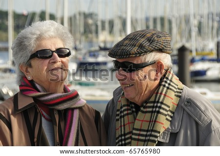 Happy old french couple walking together at the yacht harbor of Brest in Brittany, France - stock photo