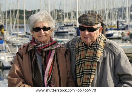 Happy old french couple walking together at the yacht harbor of Brest in Brittany, France