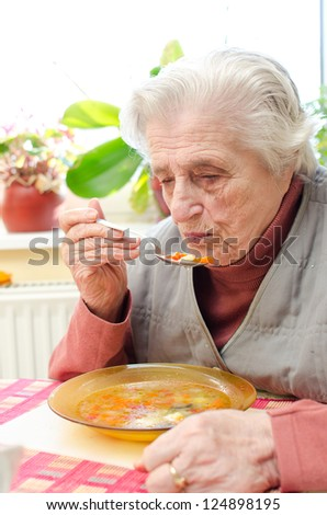 Happy old gray-haired woman eating soup