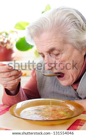 Happy old gray-haired woman eating soup - stock photo