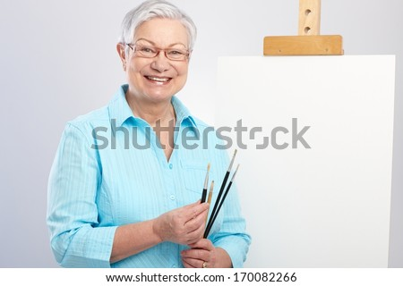 Happy old lady as hobby painter with canvas and paintbrush. - stock photo