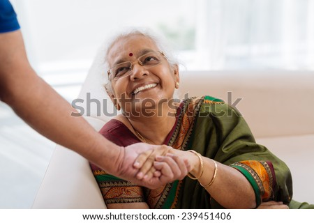 Happy old lady holding a hand of her husband and looking at him - stock photo
