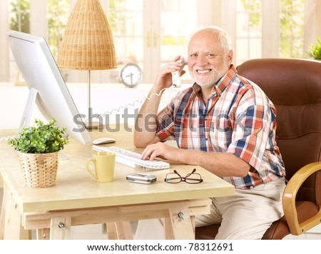 Happy old man on landline call sitting at desk using, computer, smiling, looking at camera.? - stock photo
