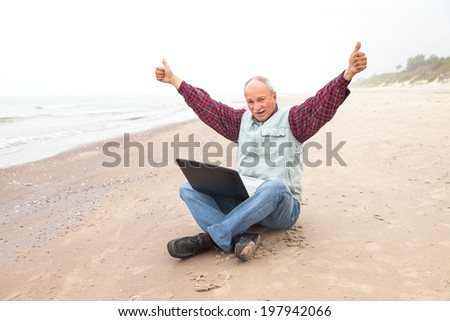 Happy old man on the beach with a laptop on a foggy day - stock photo