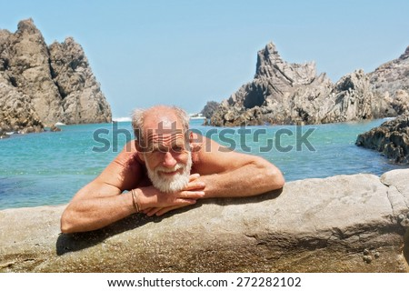 Happy old man rests on rocky beach. Shot on the Otter trail in the Tsitsikamma National Park, Garden Route area, Western Cape, South Africa.  - stock photo