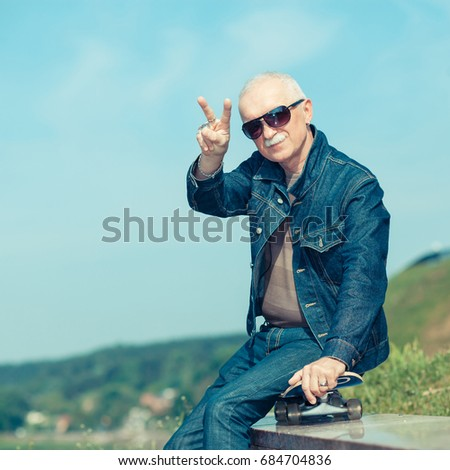 happy old man showing thumbs up. The concept of life satisfaction. Portrait of a positive gray-haired man with a skateboard. winner concept.