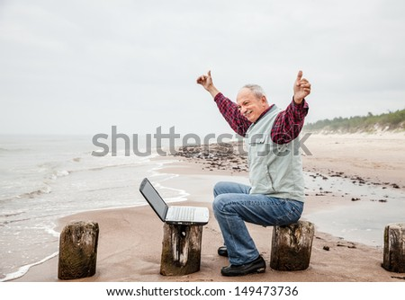 Happy old man with a laptop on the beach on a foggy day