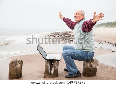 Happy old man with a laptop on the beach on a foggy day - stock photo