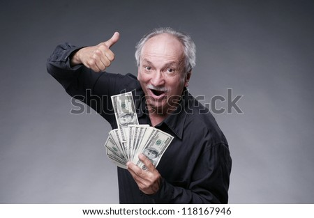Happy old man with money on a grey background