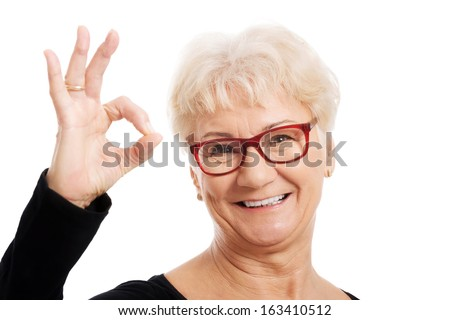 Happy old woman in eye glasses showing OK. isolated on white.  - stock photo