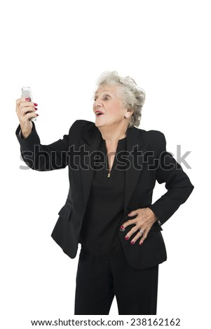 Happy old woman taking a photo of herself with a mobile phone against a white background - stock photo