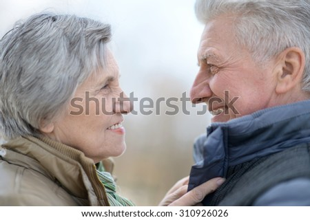 happy older couple on a walk in the park in spring - stock photo