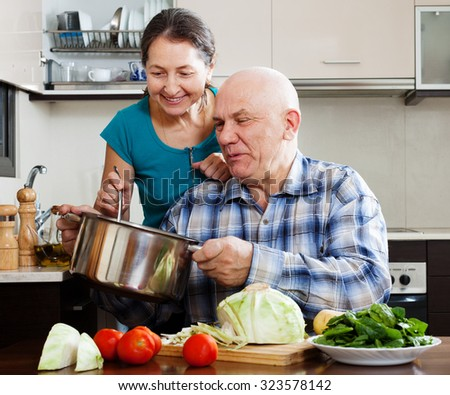 happy ordinary mature couple cooking together  lunch with vegetables in home kitchen