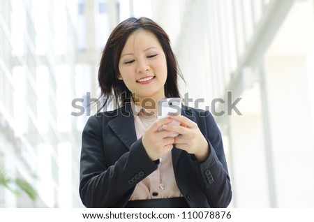 Happy oriental Asian young executive using mobile phone to online / texting / sms - stock photo