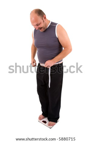 Happy overweight man standing on the scale and holding a measuring tape - stock photo