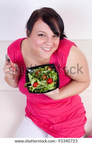 Happy overweight woman eating a salad. Selective focus. - stock photo