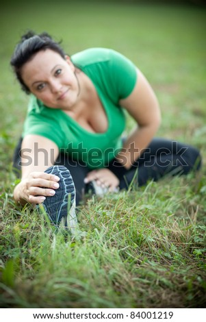 Happy overweight woman stretching in a park. Selective focus.