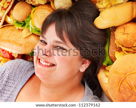Happy overweight woman with fast food. - stock photo