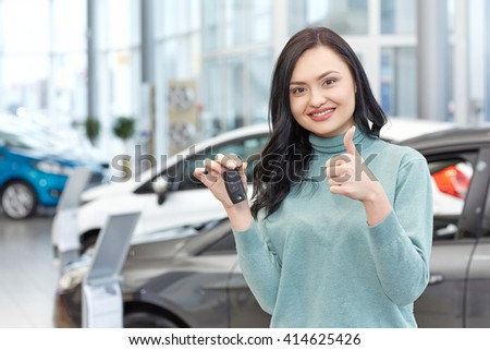 Happy owner. Horizontal portrait of a beautiful brunette woman showing thumbs up holding car keys smiling happily at the car salon