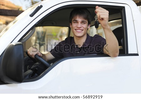 happy owner of a new truck showing car keys - stock photo