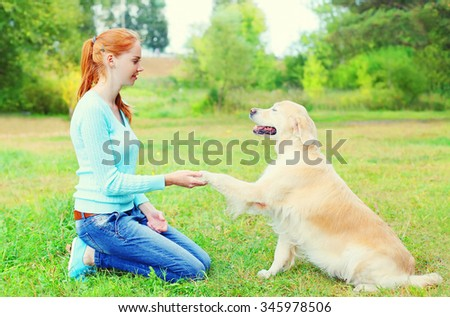 Happy owner woman training Golden Retriever dog on grass in park, giving paw - stock photo