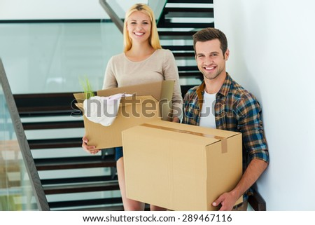Happy owners of new house. Cheerful young couple holding cardboard boxes while standing on the stairs of their new house - stock photo
