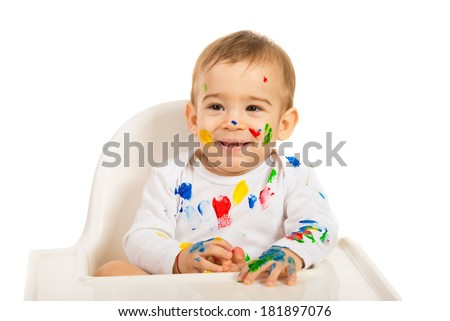 Happy painter baby at table looking away isolated on white background