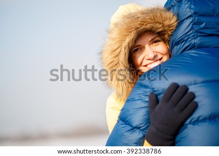 happy pair of male and female embracing ain winter outdoors - stock photo