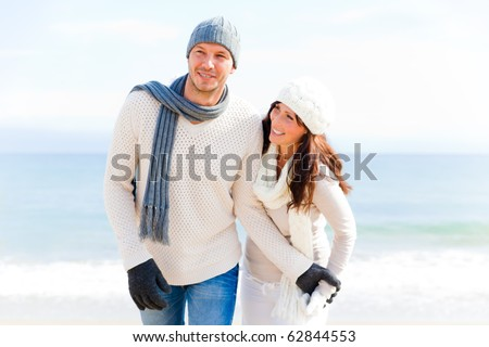 happy pair of male and female embracing and having fun wearing warm clothes outside on coast behind blue sky - stock photo