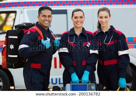 happy paramedics carrying portable equipments in front of ambulance - stock photo